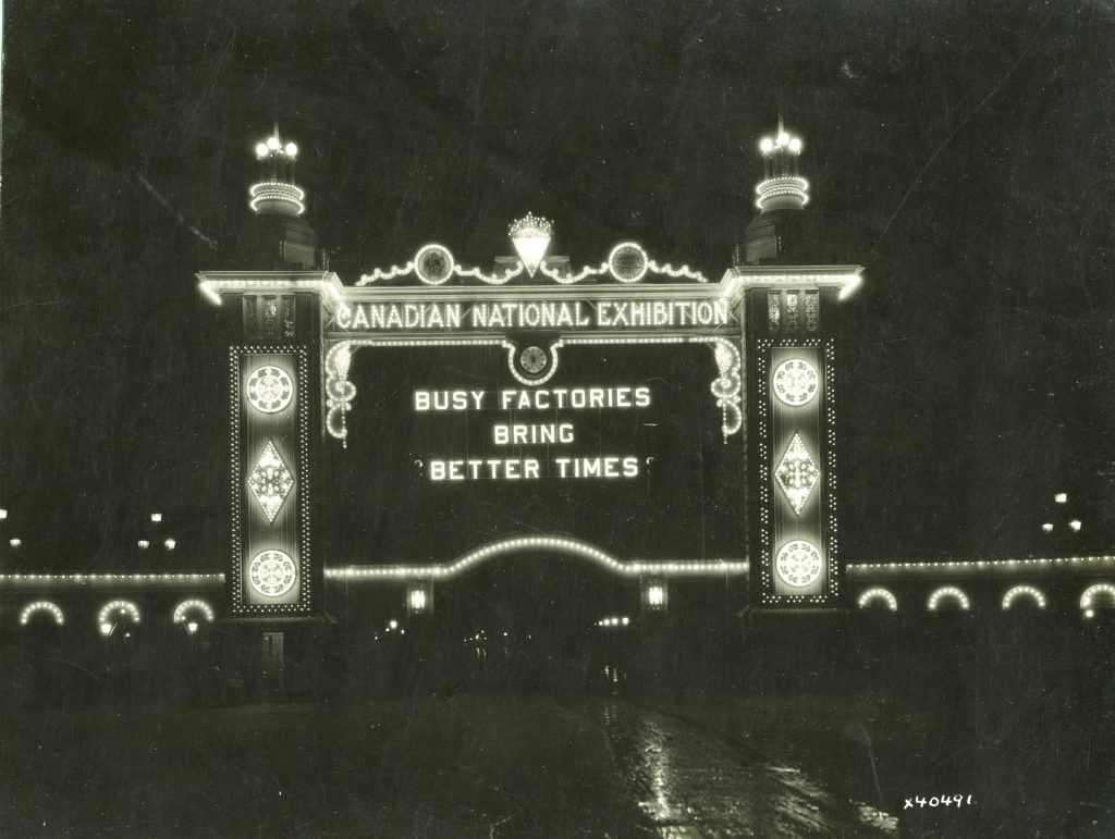"""1932 - The second Dufferin Gate lit up at night """"Busy factories bring better times"""""""