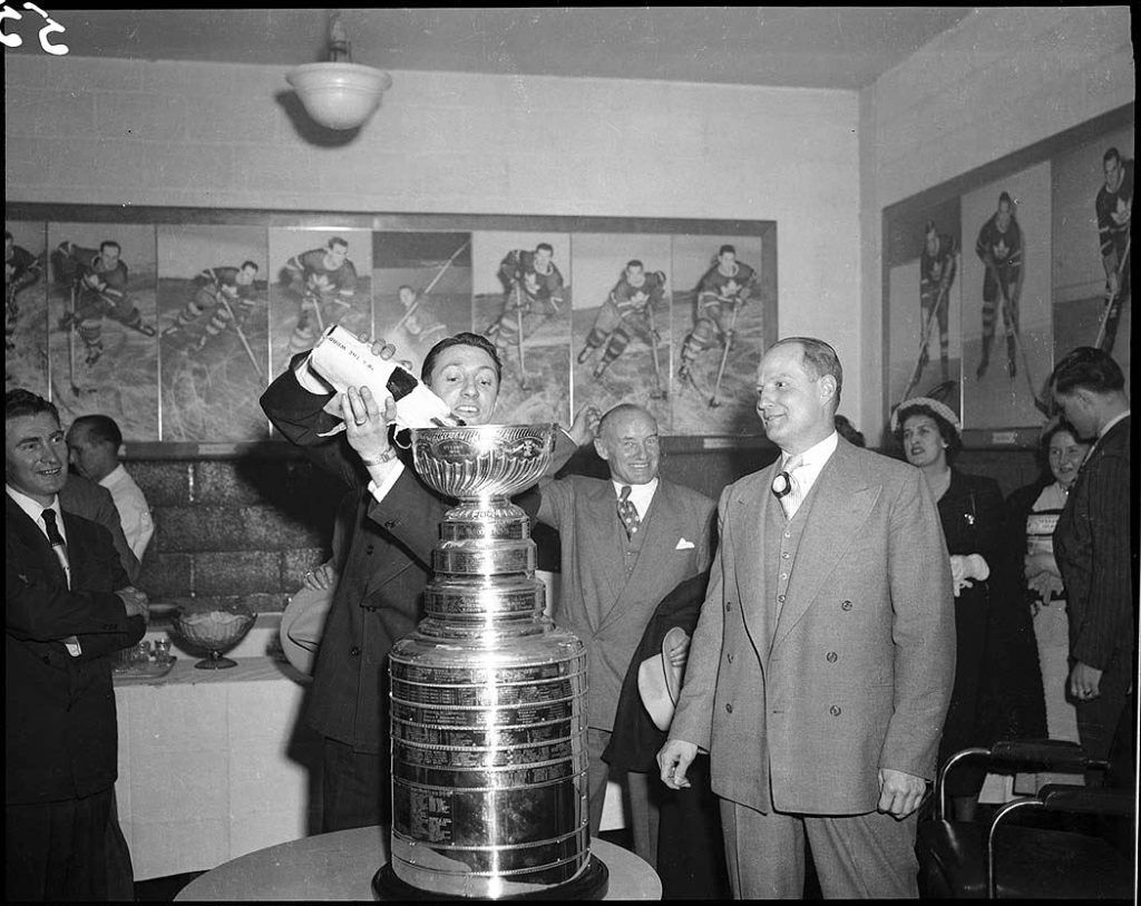 1940's - Spiff Evans pouring champagne into the Stanley Cup
