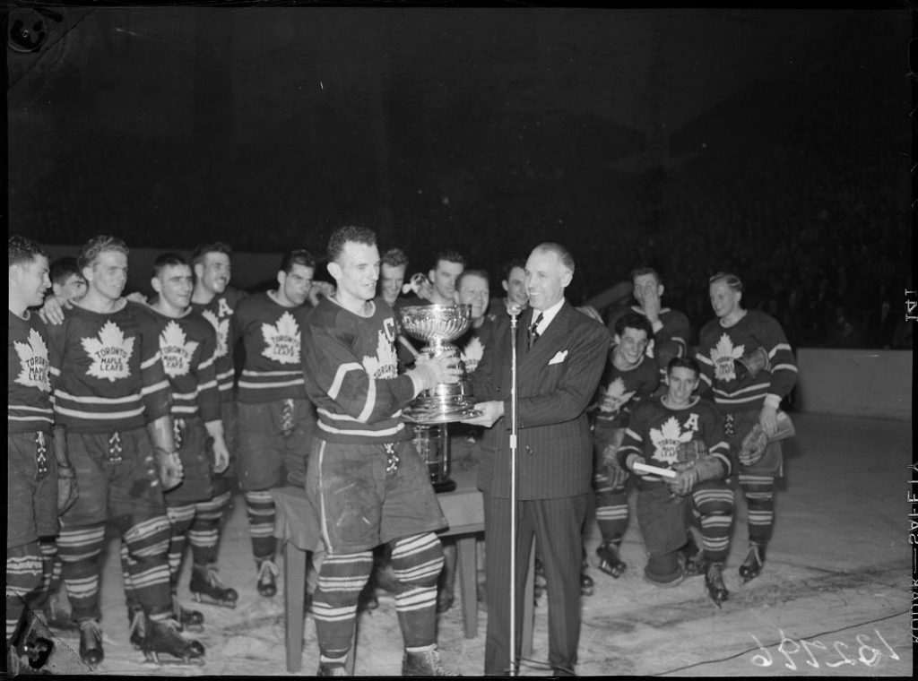 """1949 - Toronto Maple Leafs Captain, Ted """"Teeder"""" Kennedy, accepting cup from Clarence Campbell"""