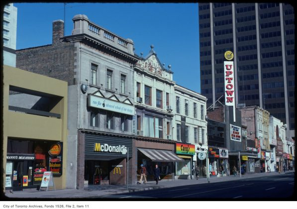 1975 - A view of stores and the Uptown Theatre along the west side of Yonge St, just south of Bloor St