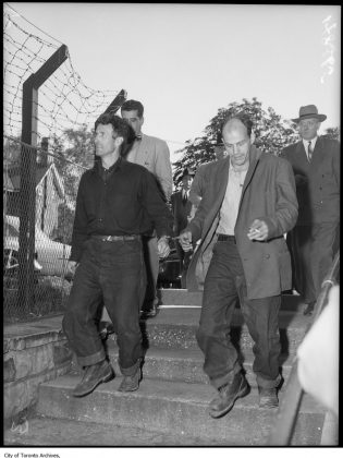 1952 - The Boyd Gang being escorted to City Hall from the Don Jail (City of Toronto Archives, Globe and Mail Fonds, Fonds 1266, Item 148365)