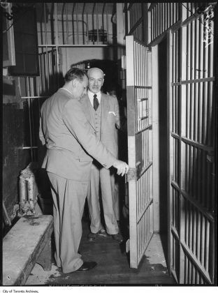 1952 - Major John Foote inspecting a cell door after a jail break at the Don Jail (City of Toronto Archives, Globe and Mail Fonds, Fonds 1266, Item 148381)