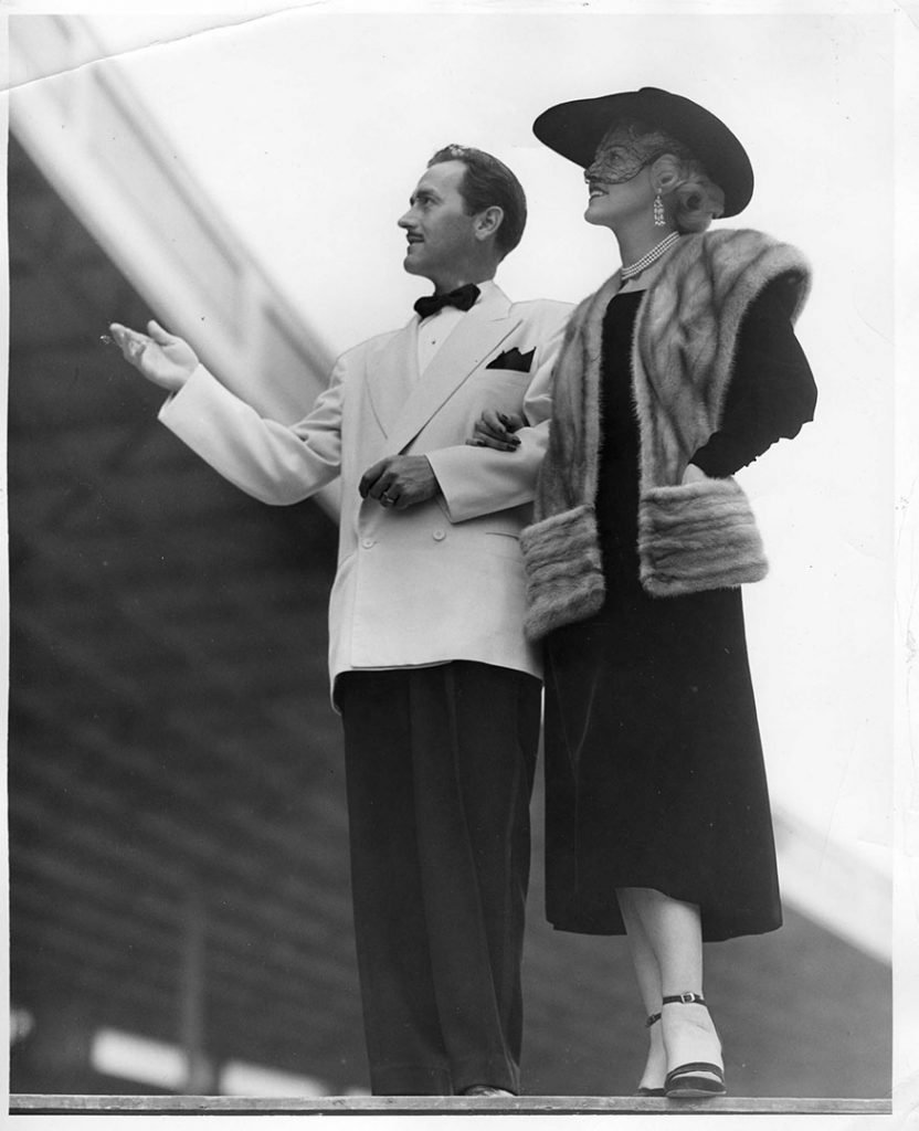 1940 - A dapper looking man sporting a white double-breasted jacket, black pants and bow tie while the woman is wearing a calf-length dress and a fur vest for an evening out at the Canadian National Exhibition
