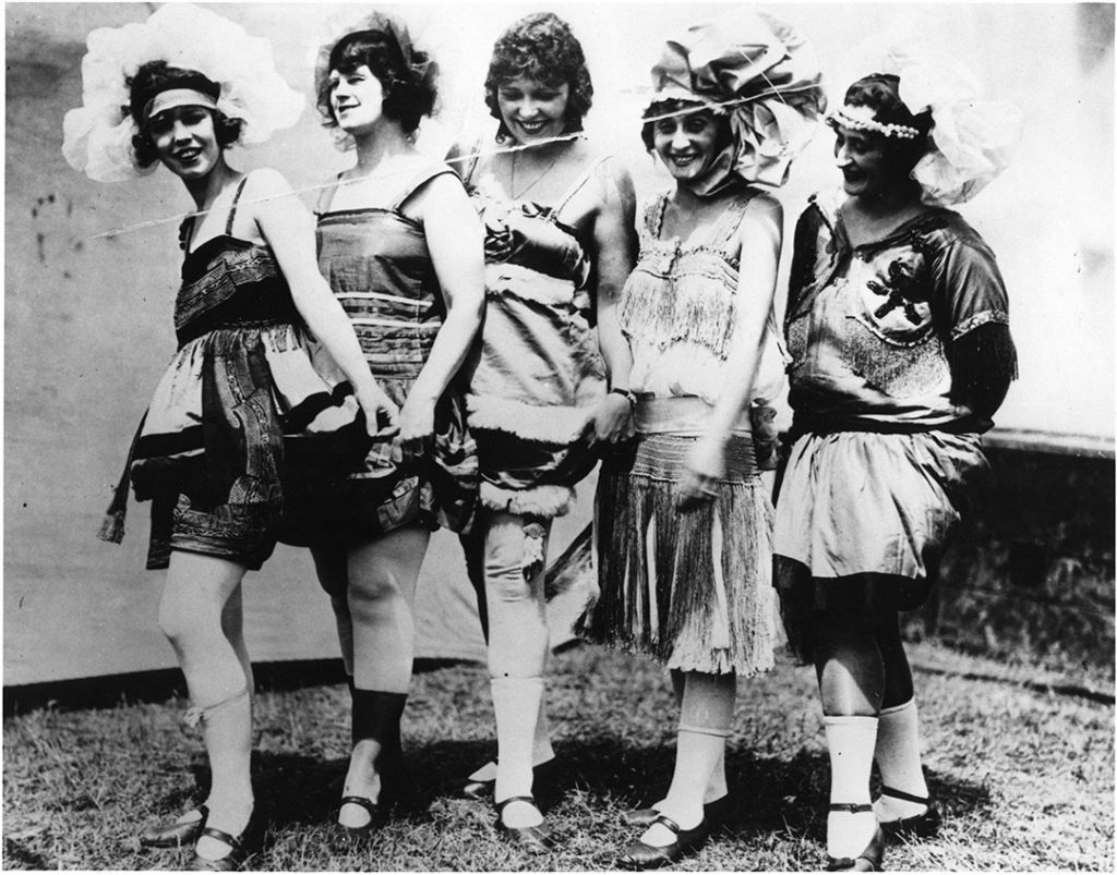 1920 - Fancy 2-piece bathing costumes with head attire, rolled stockings and beach slippers