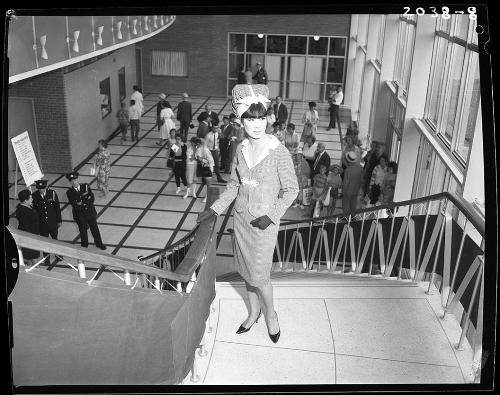 1960's - Model wearing a matching skirt, short waist jacket and snood in the Queen Elizabeth Theatre lobby at the Exhibition