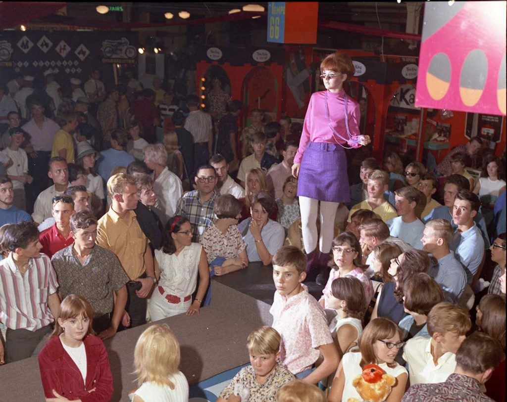 1966 - Model on the CNE fashion show runway wearing a funky purple mini-skirt, pink mock neck top, boots, long beaded necklace and tiny sunglasses