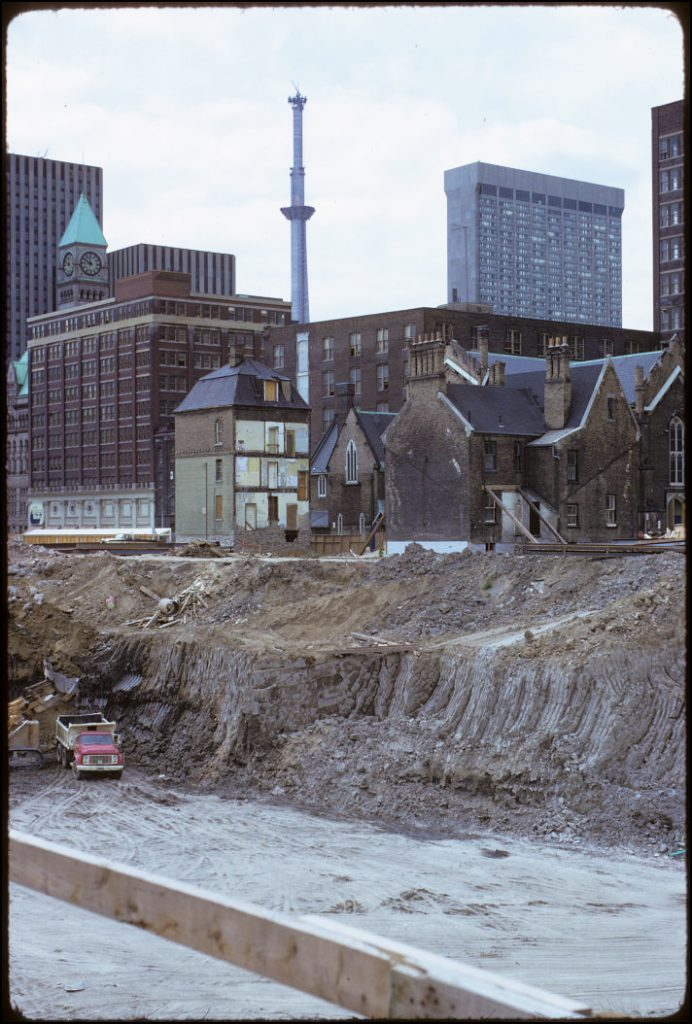 1974 - Scadding House. Rectory, Church of the Holy Trinity and view of excavation of the Eaton Centre with construction of CN Tower, looking southwest