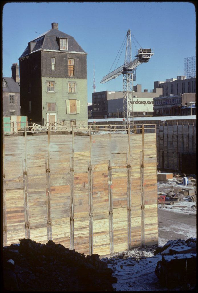 1975 - Scadding House and foundation for the Eaton Centre with Dundas Square in background, looking northeast