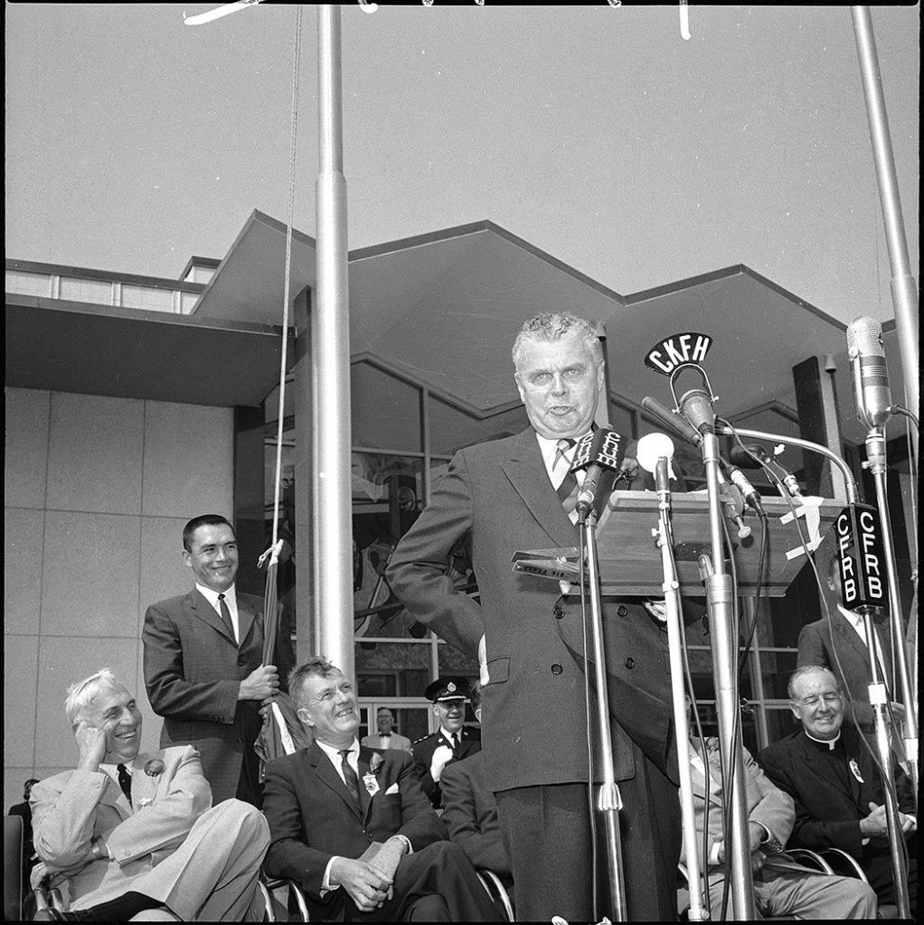 1959 - George Diefenbaker (at mic) and George Armstrong (standing by flag pole) in front of the Hockey Hall of Fame on Exhibition grounds