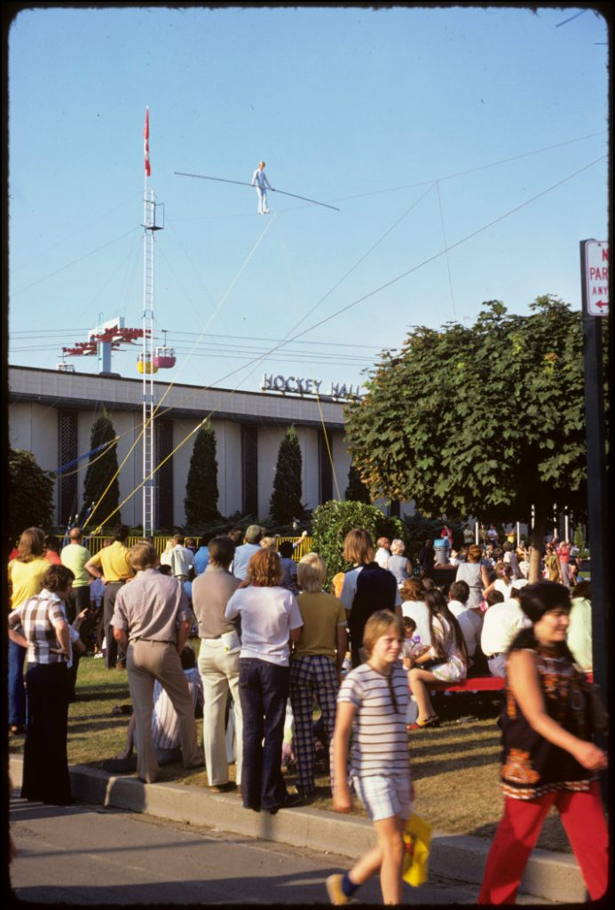 1970's - Crowds watching a tightrope walker over the Hockey Hall of Fame at the CNE