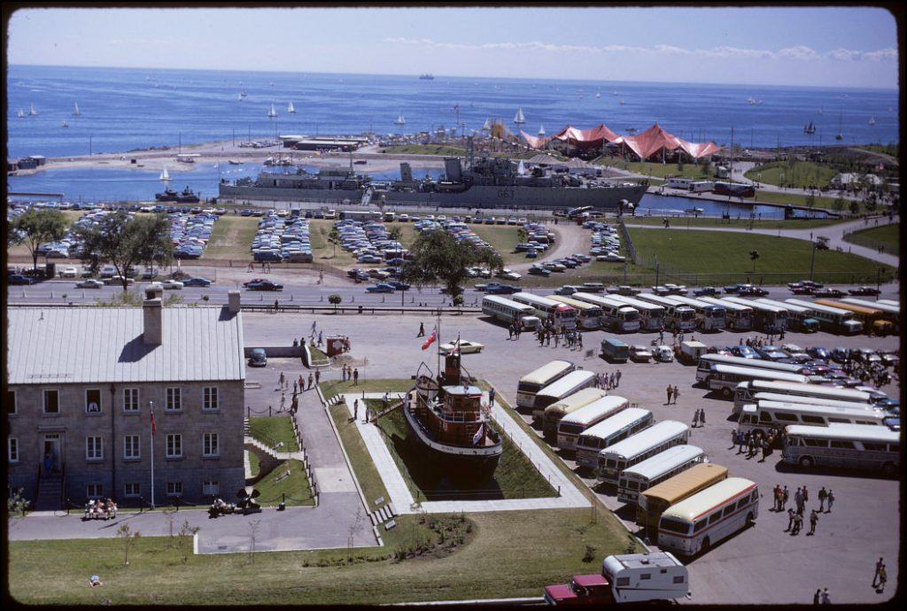 1960's/70's - A view from Exhibition grounds towards the bus parking lot, Stanley Barracks, Ned Hanlan boat, HMCS Haida and Lake Ontario, looking south