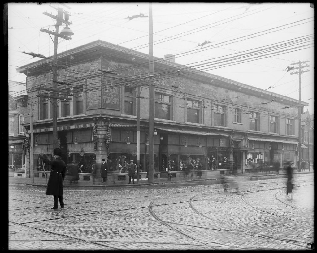 1922 - Policeman in a fur busby directs traffic at Yonge and Bloor Sts in front of Stollery's, Humphrey gas arc lamps extending from the windows