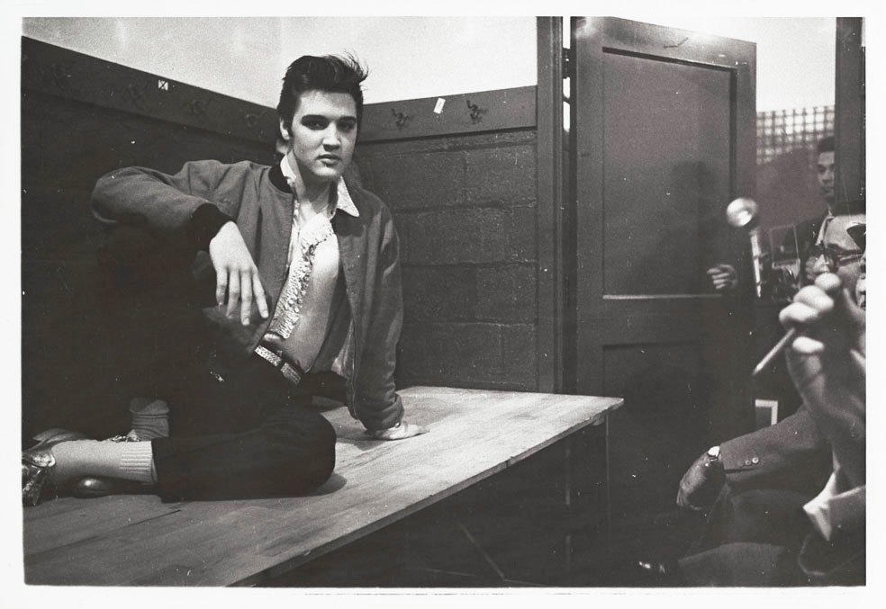 1957 - Elvis Presley on a table answering questions from journalists at a press conference, after his performance at Maple Leaf Gardens