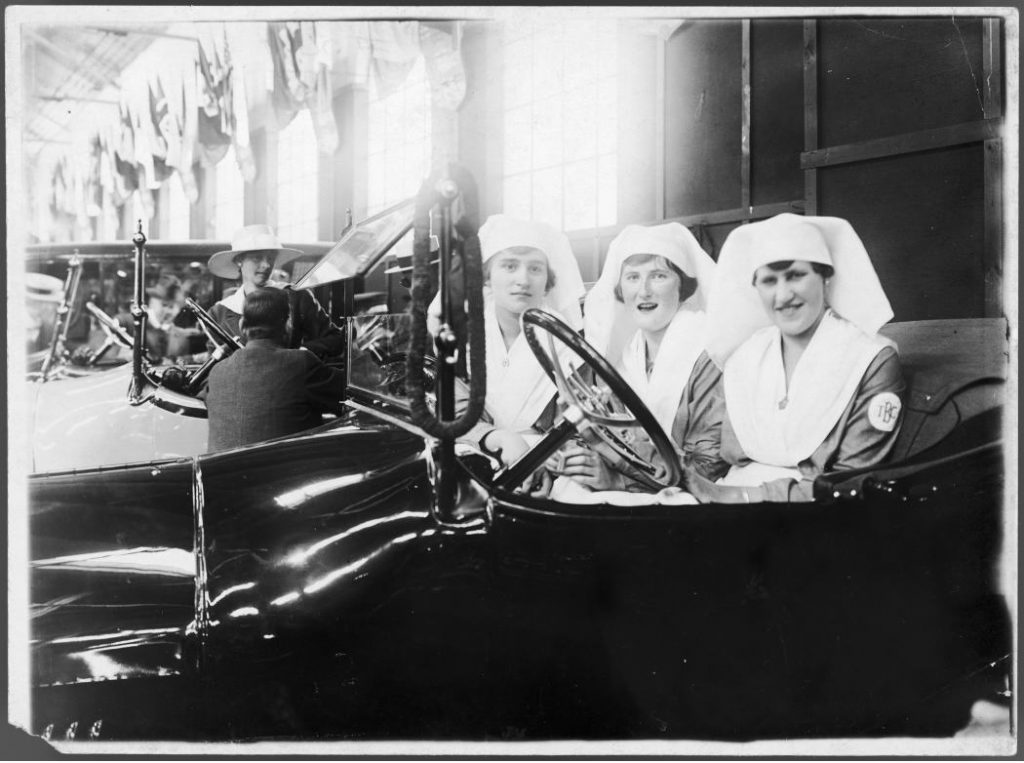 1912 - Three nurses in a car at an auto show at the Armouries