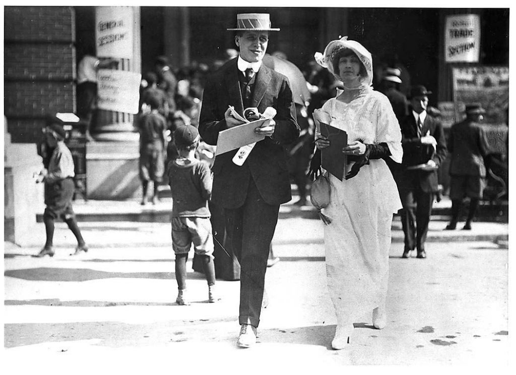 1911 - A couple enjoying a day out at the Canadian National Exhibition - the woman is wearing a tea dress and fancy hat while the man is in a 3-peice suit wearing a straw boater hat