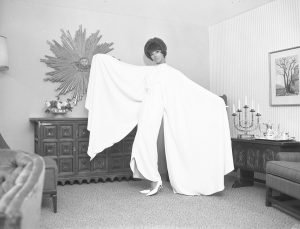 1960's - Model looking glamorous in a white dress with large angel sleeves at a CNE furniture exhibit