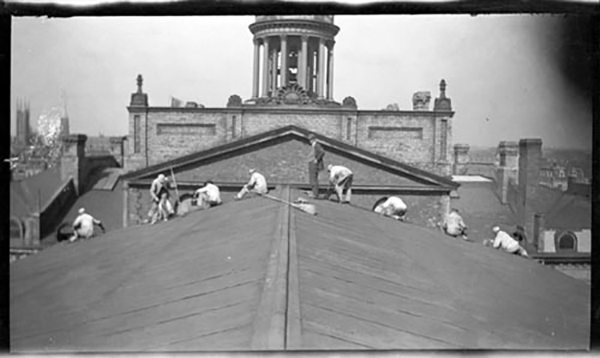 1920 - Men with brooms on top of St Lawrence Market North roof with the Hall cupola in the background, looking north